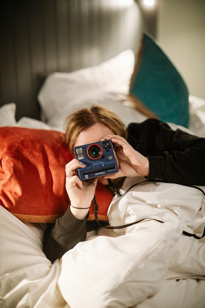 Hotel guest laying on double bed with camera